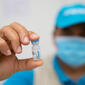 hand holding vaccine vial with blurred, masked face of health worker in background